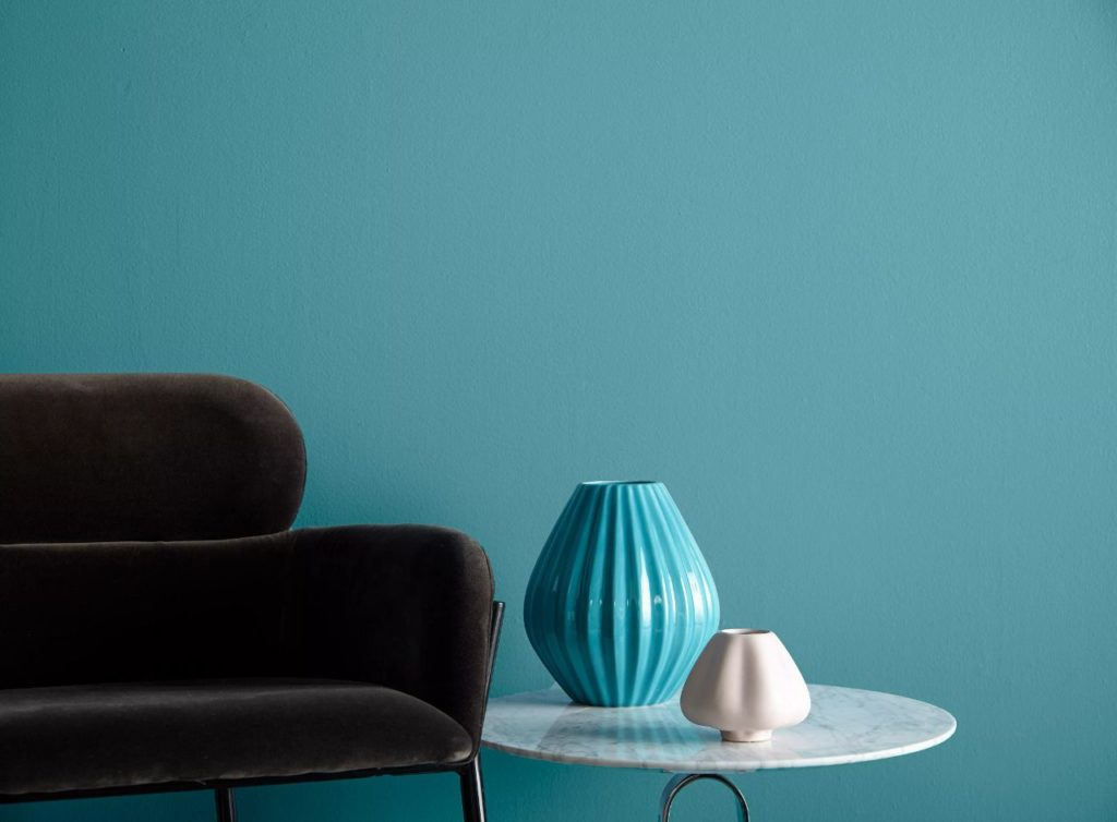 A comfy modern sitting area featuring a medium blue green color on the wall called Caribe.