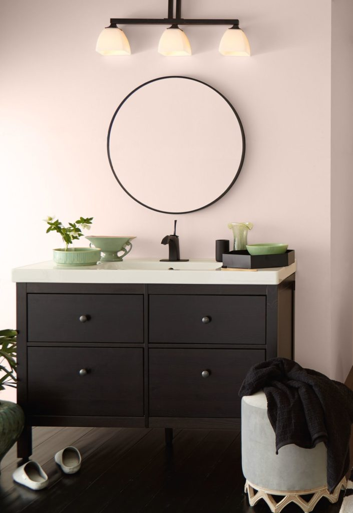 A modern powder room featuring a soft pink wall color called Seaside Villa, the vanity furniture piece is dark wood. Green, black and gray accents complete the room.