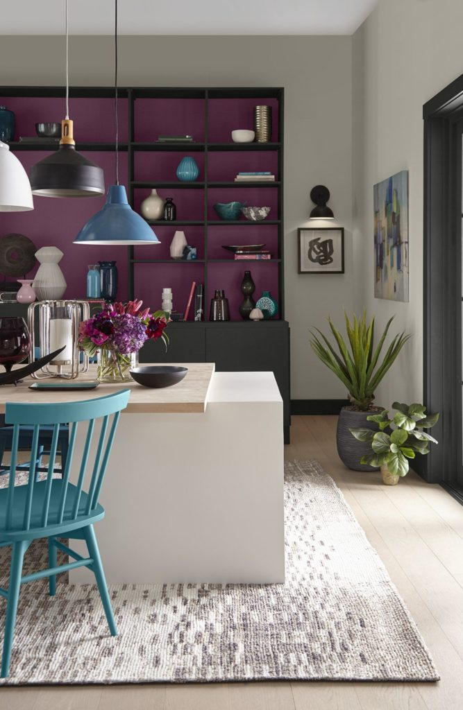 An eclectic dining area with an accent bookshelf as one of the focal points.  The outer bookshelf features a black color called Broadway and the back of the shelves are not quite pink and not quite purple, they're painted in an accent magenta color called Euphoric Magenta.