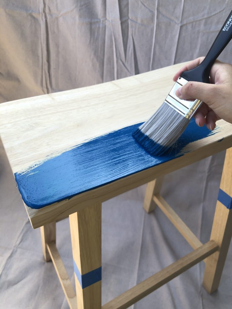 This image shows a stool being painted in Nocturne Blue.