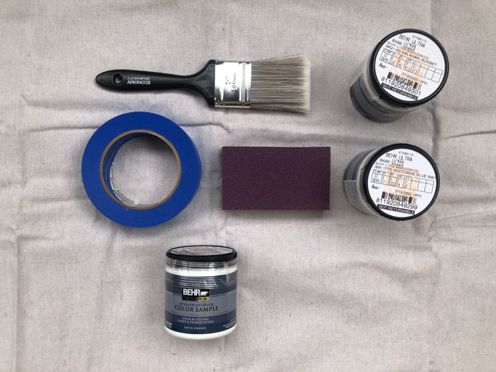 This image shows the products used for this project.  A paint brush. Painters Tape. Sanding Block. And three 8 oz. samples.