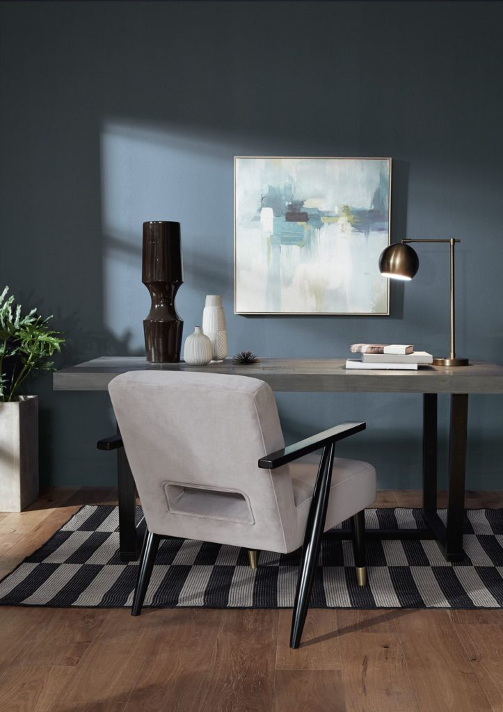 A chic office featuring a blue color on the wall called Jean Jacket Blue. The décor elements are a mix of contemporary and some more traditional pieces, including a brassy lamp and a comfy upholstered chair.