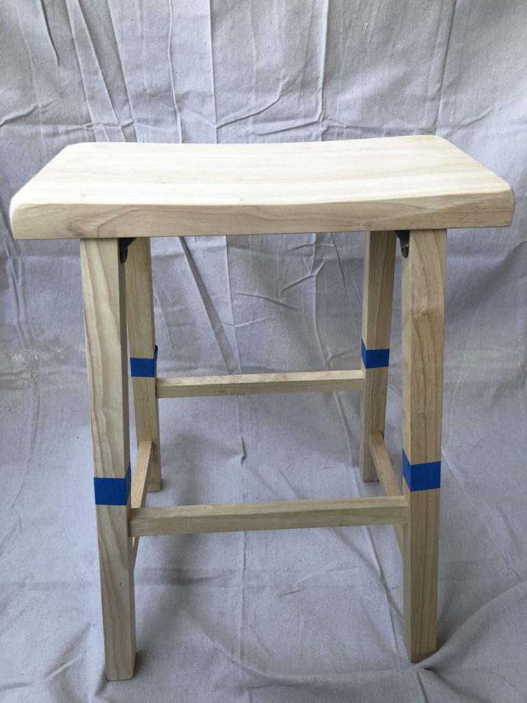 First this is the bare wooden stool that was taped off in the areas I wanted to paint.