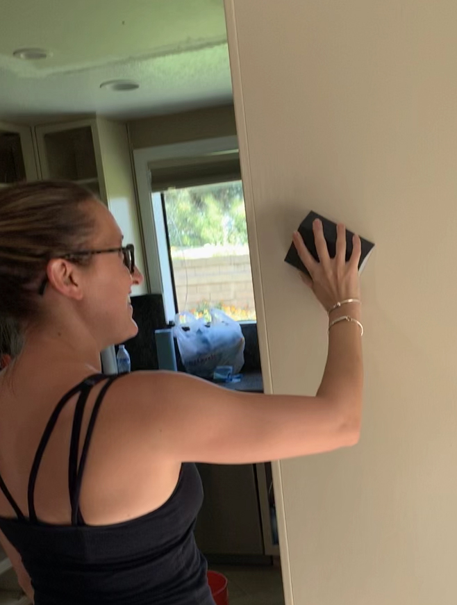 image showing person sanding the wall.