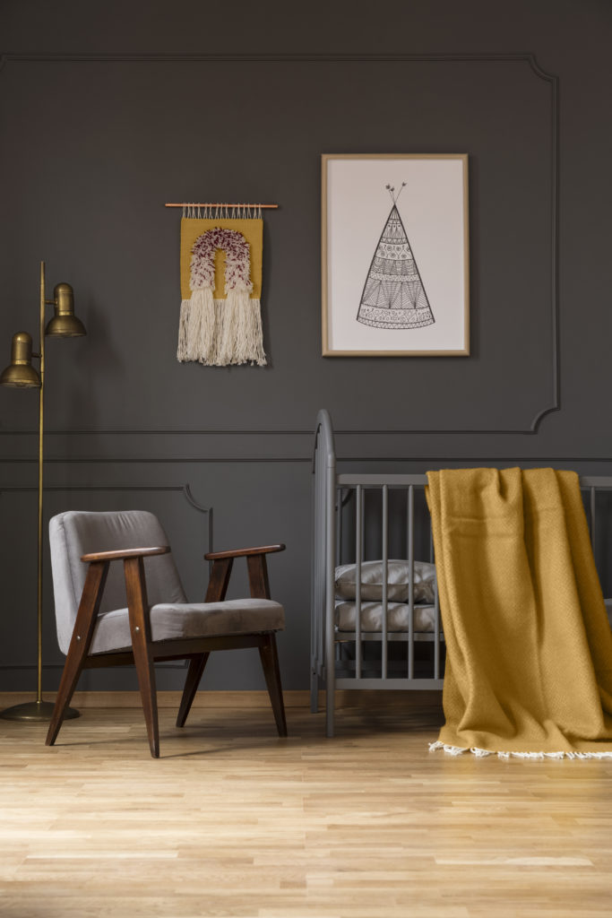 A gray nursery and crib, décor elements include a wall hanging accessory and a yellow blanket.