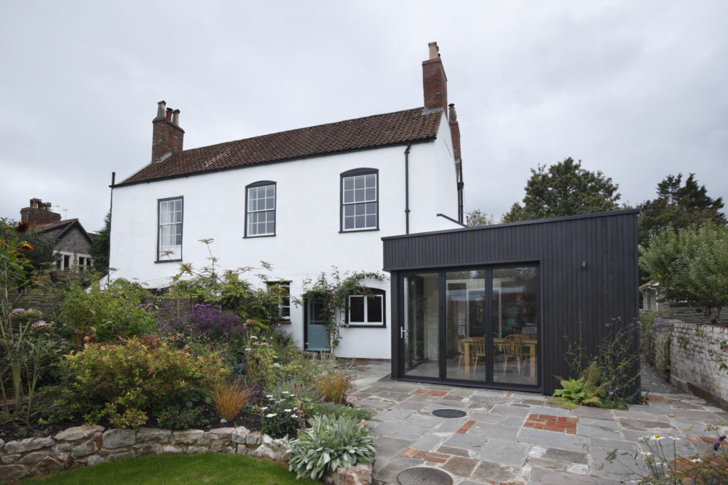A period home painted in white color and a modern extension built onto the side painted in a black color.