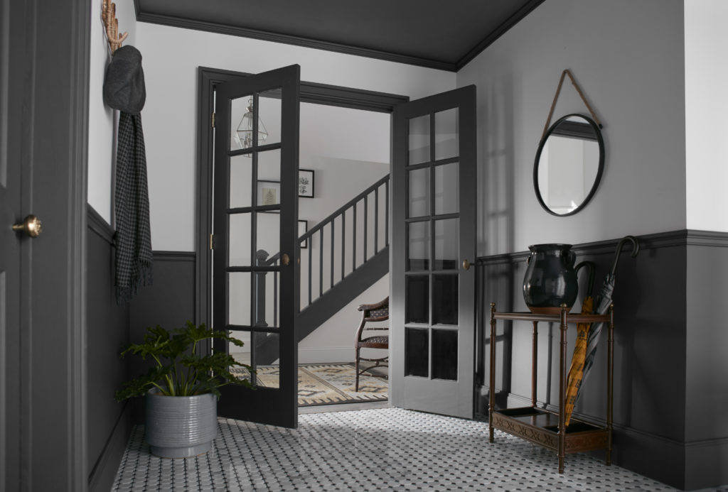 An elegant light gray and black room-to-room interior space.  A  hallway, foyer & staircase area  with tile flooring, black lower walls, and woodwork details. The simple combination of the colors is just beautiful. The round mirror on  the wall and the natural dark wood furniture add a classy vibe to the hall.