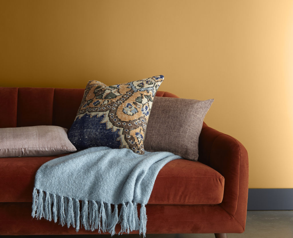 A simple vignette featuring Saffron Strands and a retro sofa and cozy pillow and blanket.