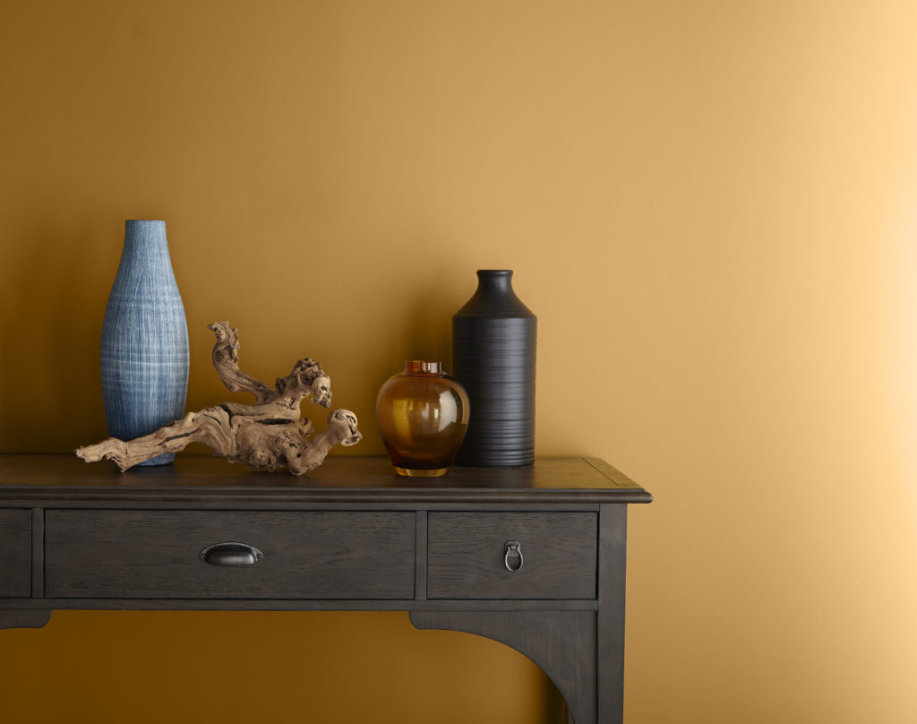 A simple vignette featuring Saffron Strands on the wall and a traditional desk ceramic and  glass vases and, a dried grape wood branch.