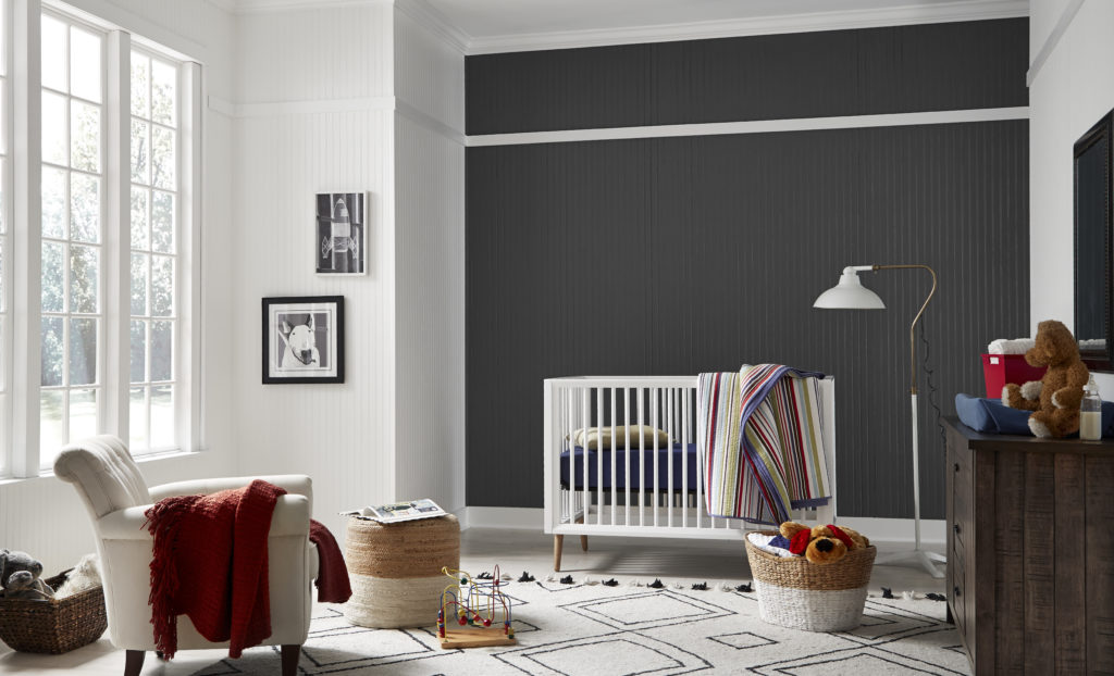A black shiplap feature wall in an ample and well-lit  modern farmhouse nursery room.   A modern white crib with colorful bedding. The bold contrast of light and dark gives this nursery a modern feel while the colorful accent provide a touch of whimsy.