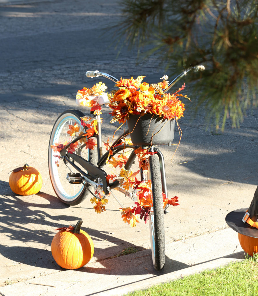 A bicycle decorated with fall colored leaves in red, orange and yellow.
