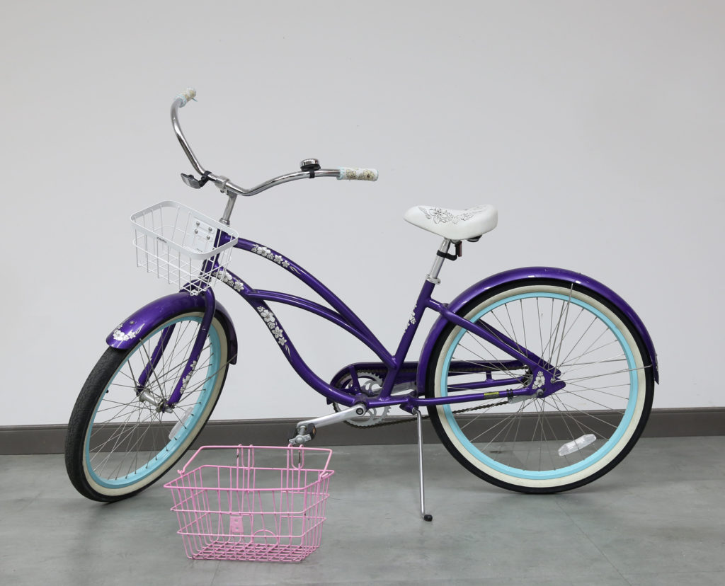 An old purple colored bike with white flowers.