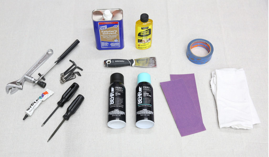 A drop cloth with tools placed on it. The tools are from the list below showing what is needed to spray paint a bike.