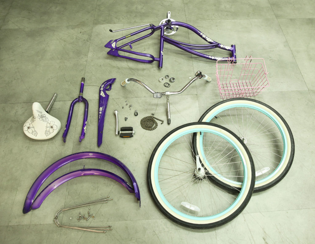 Image of a bike disassembled with all the pieces sitting on the ground.