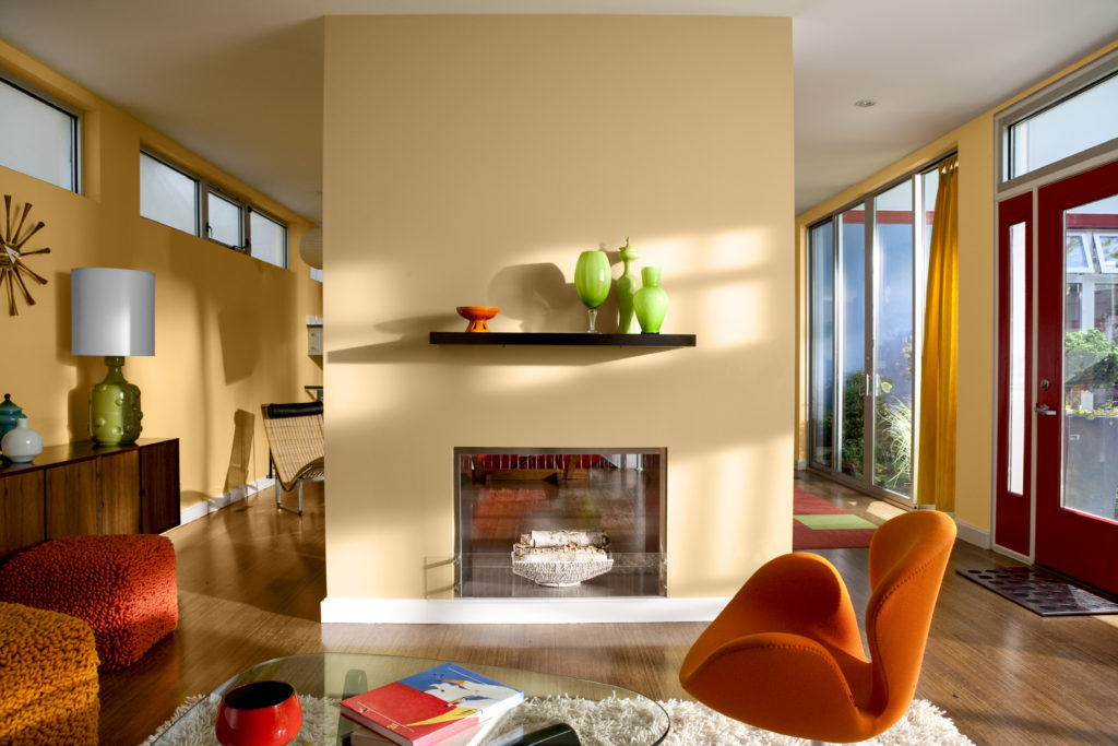 A brightly colorful mid-century home interior, this living room area is featuring tone on tone walls, a fireplace wall painted in a light gold color called Cellini Gold. An accent wall featuring color of the month, Saffron Strands.