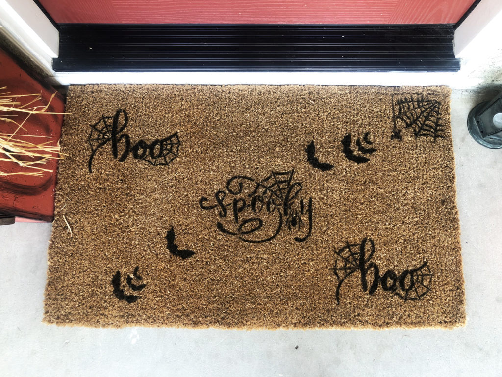 This image is a down shot of the doormat. The doormat stencils feature Spooky, BOO, Bats, and spider webs.
