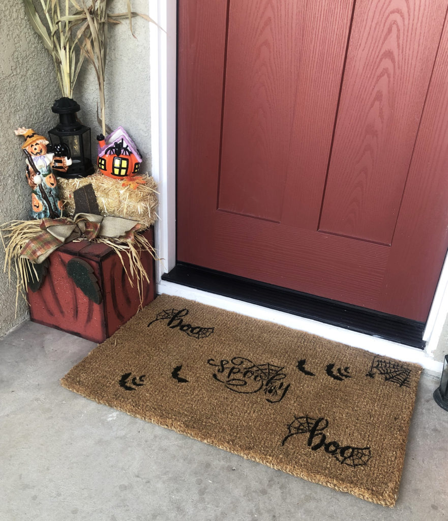 This image shows a closer look at the doormat and halloween decor surrounding it.