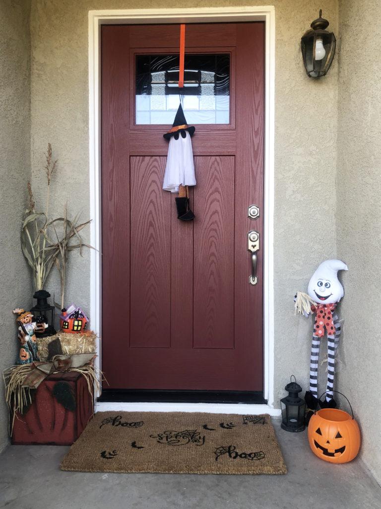 This image features a Halloween stencil doormat. Surrounding the doormat is festive halloween decor.