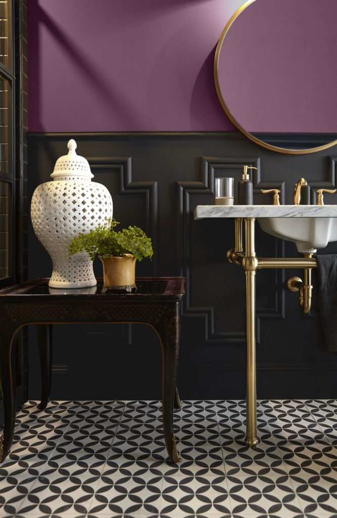 A moody and highly sophisticated two-tone powder room, the upper wall painted with a plum color called Euphoric Magenta and lower wall painted with a black color called Broadway. The warm tone metallic hardware and the fun black and white floor tile add charm to this space.
