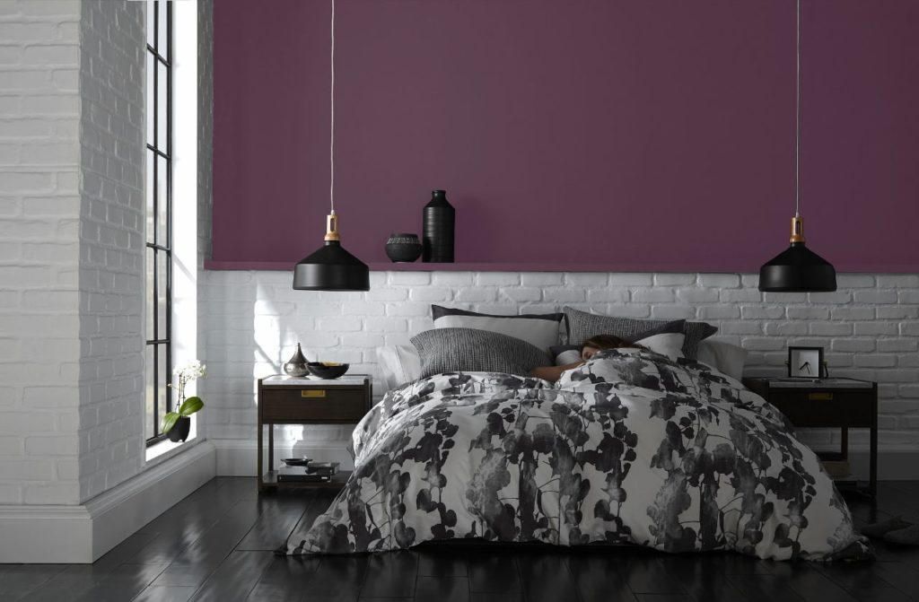 An industrial chic bedroom, the bottom wall is white painted brick and upper wall is painted with an accent color called Euphoric Magenta.  The bed is dressed in black and white oversized floral bedding.
