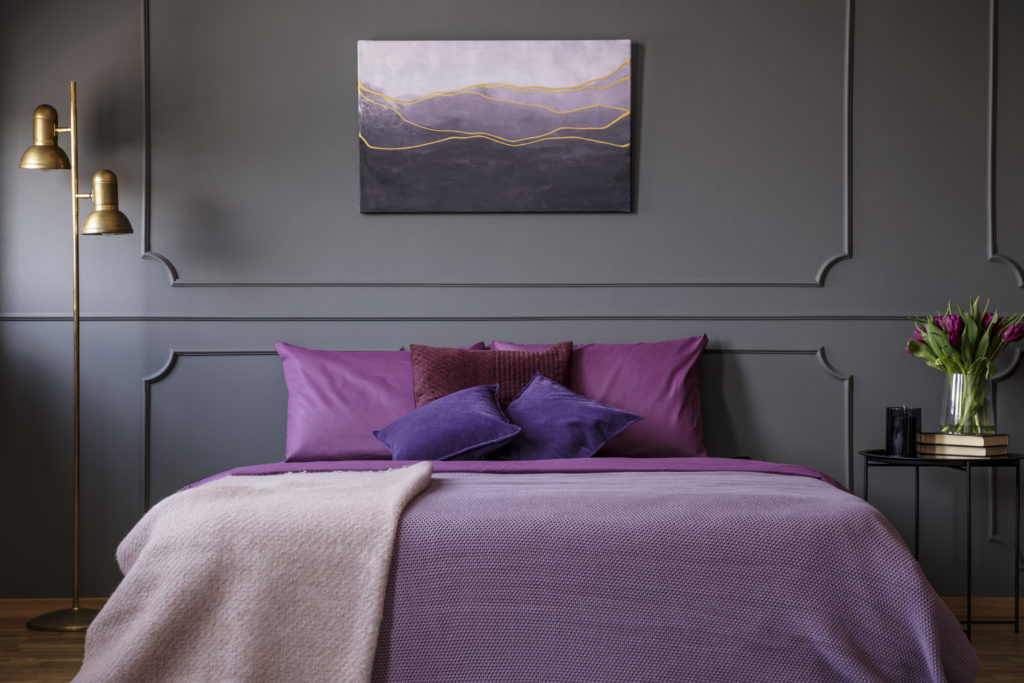 An elegant bedroom with painting on the wall and a big bed in the center, the bed is dressed in this striking magenta hue which adds  dramatic impact to the space.