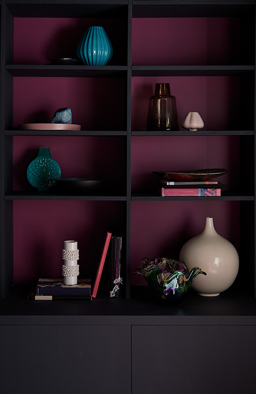 A modern and elegant built-in, a magenta background color creates a dramatic backdrop for displaying eclectic décor pieces.
