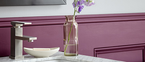 A close-up detail of a half bath wall and sink, the small space features a statement magenta lower wall.