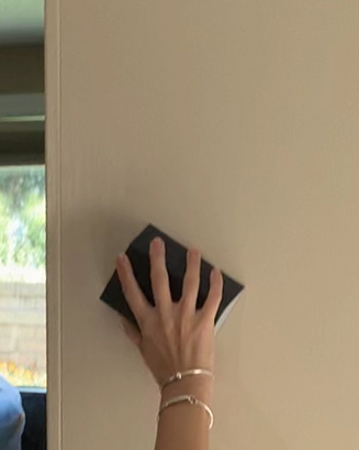 hand sanding wall.