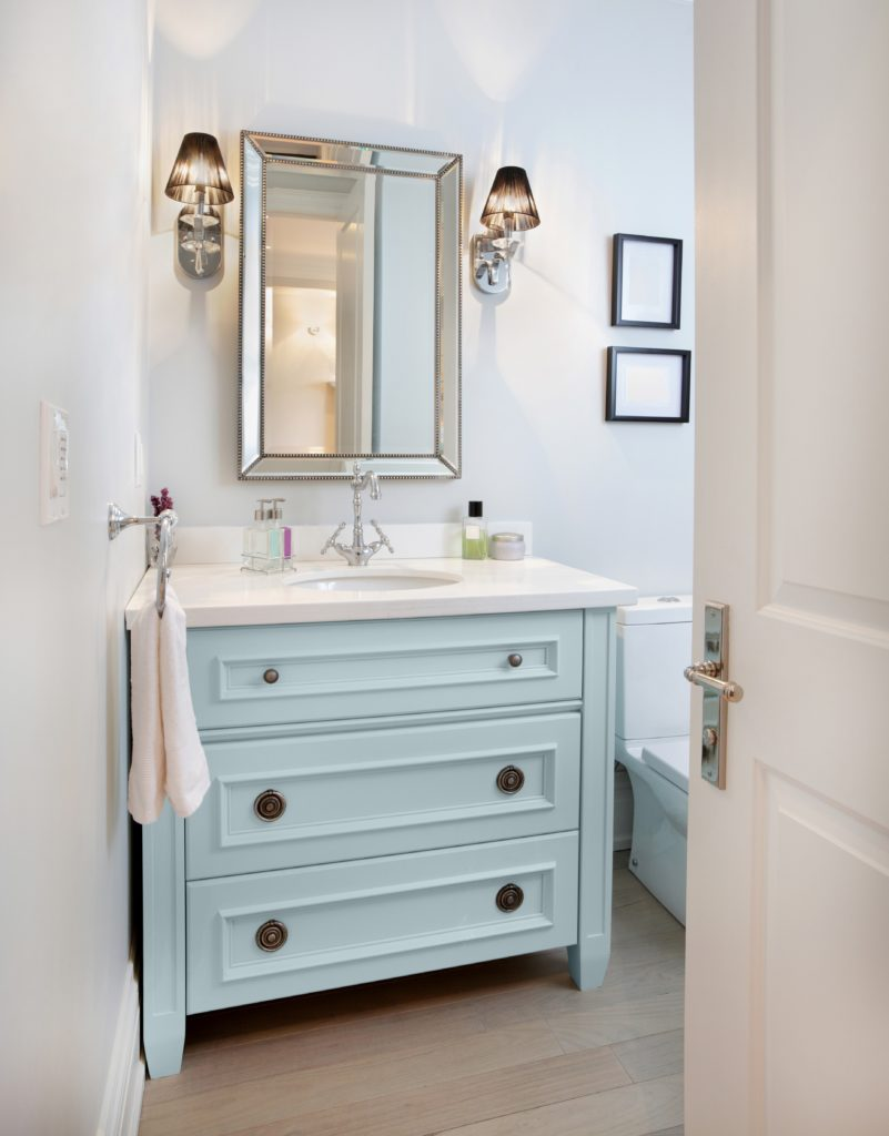 A nice small bathroom with light blue vanity, the room is painted in white paint the vanity is painted in a color called Dayflower.
