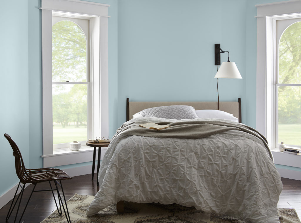 A casual bedroom, there is a window on both side of the bed which lit up the room and create an open and airy feel. The walls are painted in a light blue color called Dayflower.