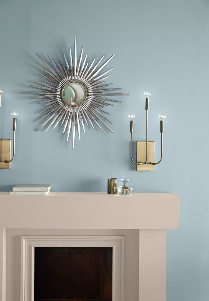 A blue wall painted in a light blue color called Dayflower. A modern fireplace decorated with a chrome sunray mirror and two monumental metal lamps.
