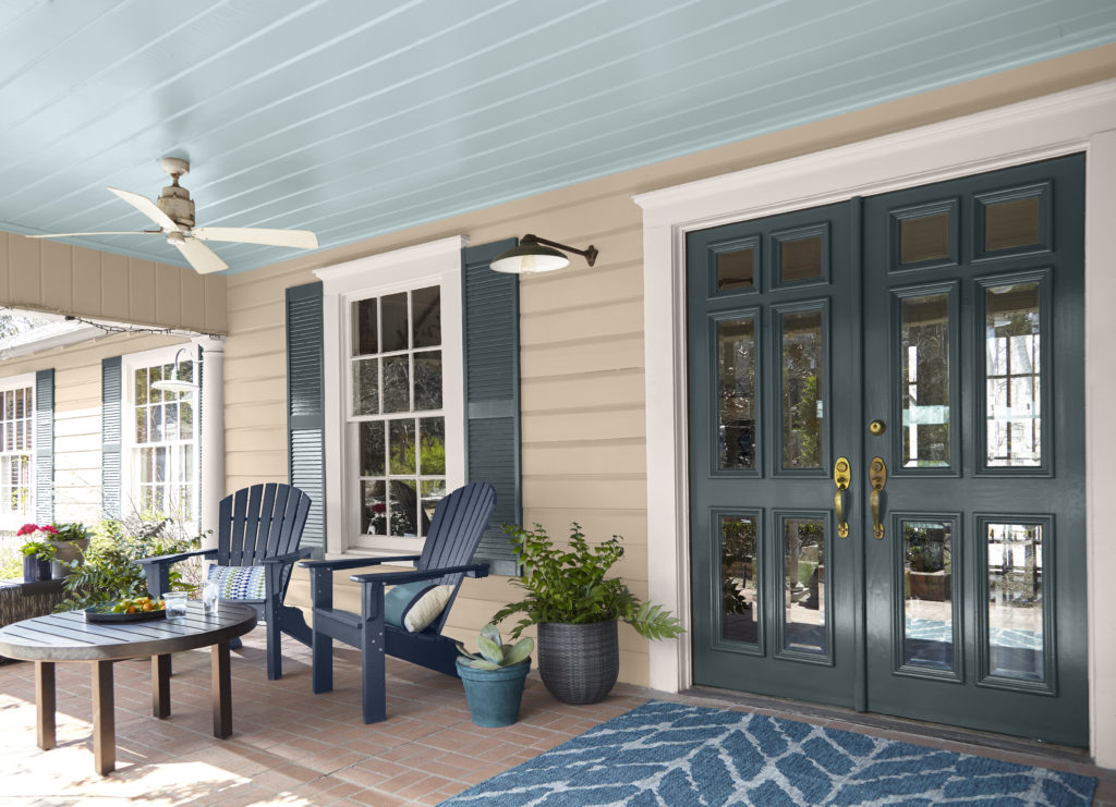 The porch of a large Traditional home, the house is painted in a light tan color and ceiling painted in a light blue color called Dayflower. There is a large double door and shutter painted in a dark green color.