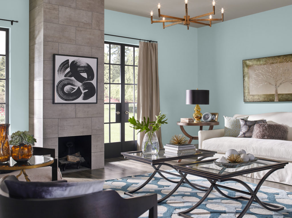 A modern-eclectic decorated  living room with dark natural wood tone furniture,  wall décor elements. The color featured on the wall is called Dayflower.