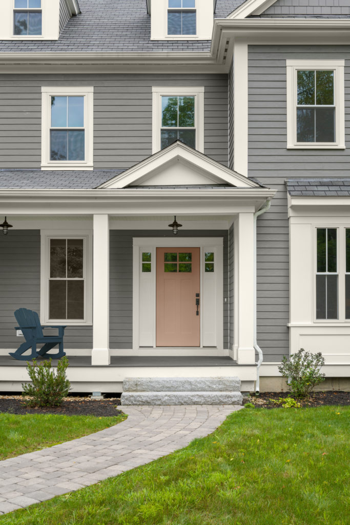 The front side of a home exterior, the siding of the house  is painted in a gray color called Barnwood Gray. The front door is painted in a terra cotta color called Canyon Dusk.