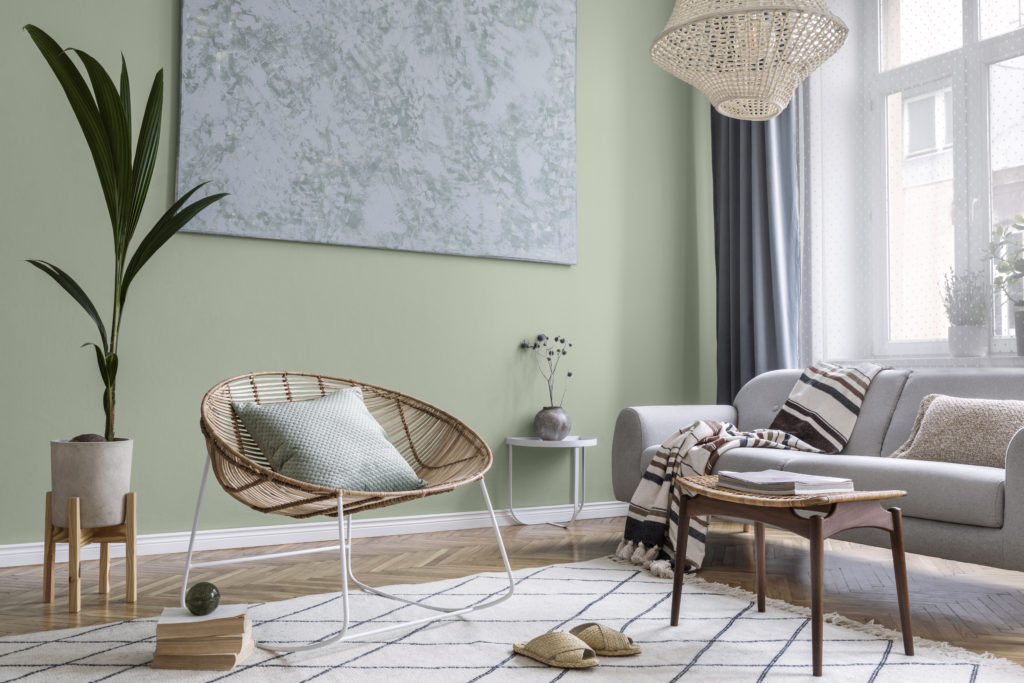 Interior design of living room at modern home with stylish furniture. The room feel well lit with natural light and the walls are painted in a mid-tone green called Jojoba.
