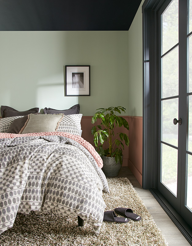 A casual bedroom painted in warm and relaxing color combination, the ceiling, trim and door is painted in an soft black called Broadway, the upper wall was painted  a mid-tone green and the lower wall features an orang-y brown called Modern Mocha.