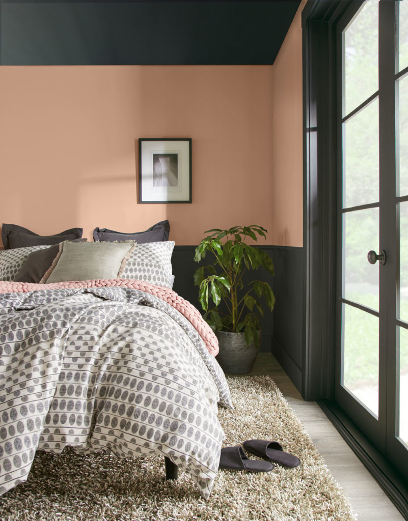 A two tone cozy bedroom, the lower wall is painted in a soft black color called Broadway and the upper wall is painted in a terra cotta color called Canyon Dusk.