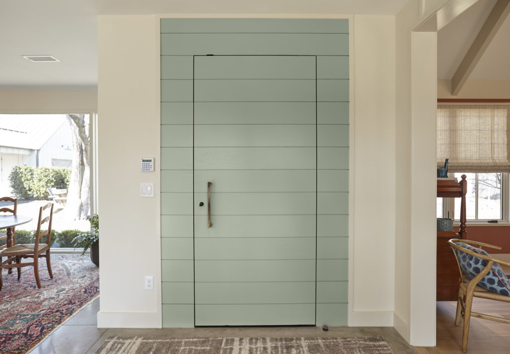 The main entry of an eclectic home, the door is painted in a mid-tone green called Jojoba.  The walls are painted in an off white called Smoky White which allows the green door to pop.