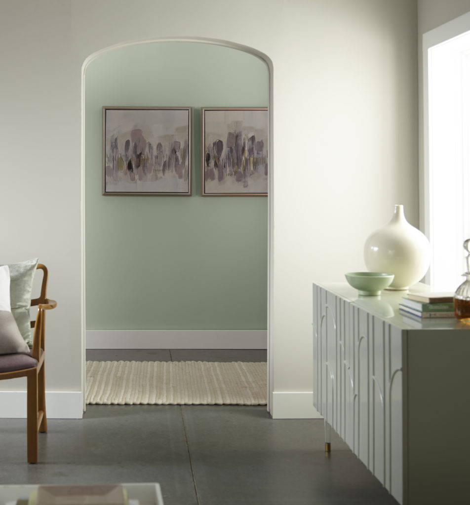 The vertical view of a living room and a hallway, both home interior areas are well lit by the natural light coming in through a large window. The living room are is painted a light warm gray and the hallway is painted in a green color called Jojoba.