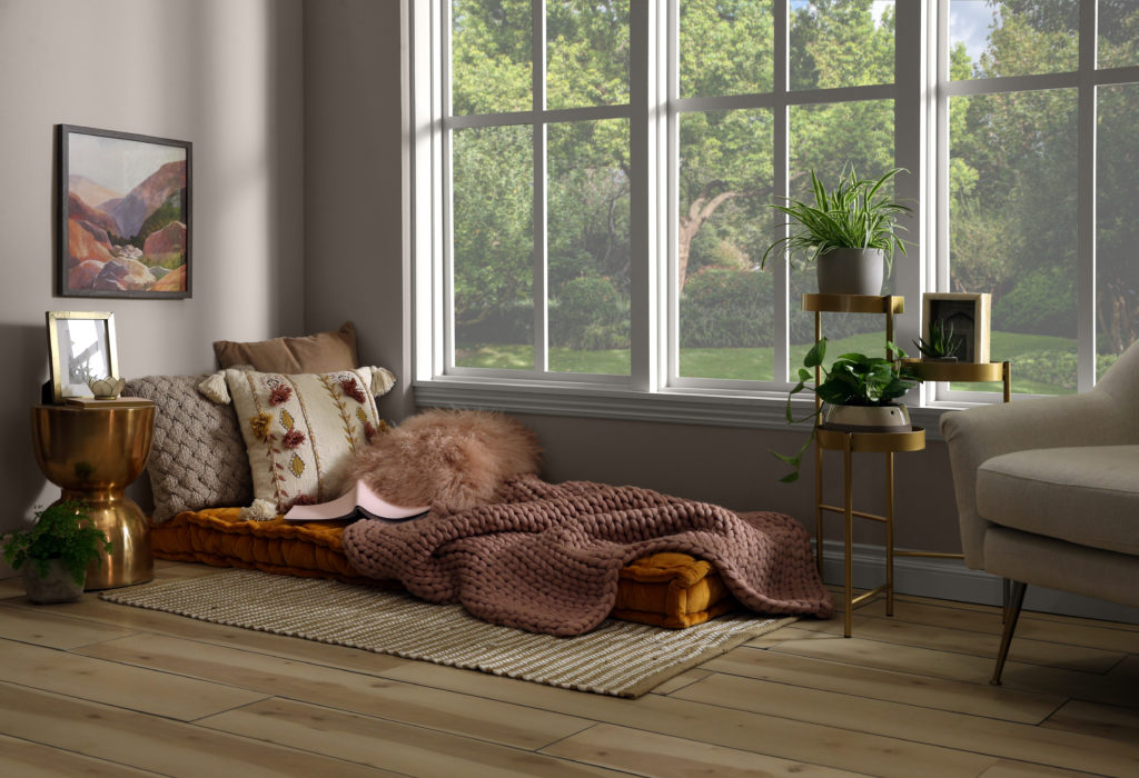 A full horizontal image of cozy corner. This space has been carved in a room of the home. There is a large window that allow light into the room.  The color on the wall is a light neutral called Doeskin Gray.