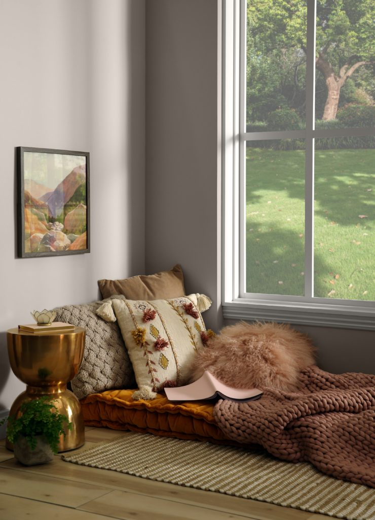"""A carved corner in the home that has been turned into a """"sheltered"""" area for relaxing. There is a large window that allow light into the room.  The color on the wall is a light neutral called Doeskin Gray."""