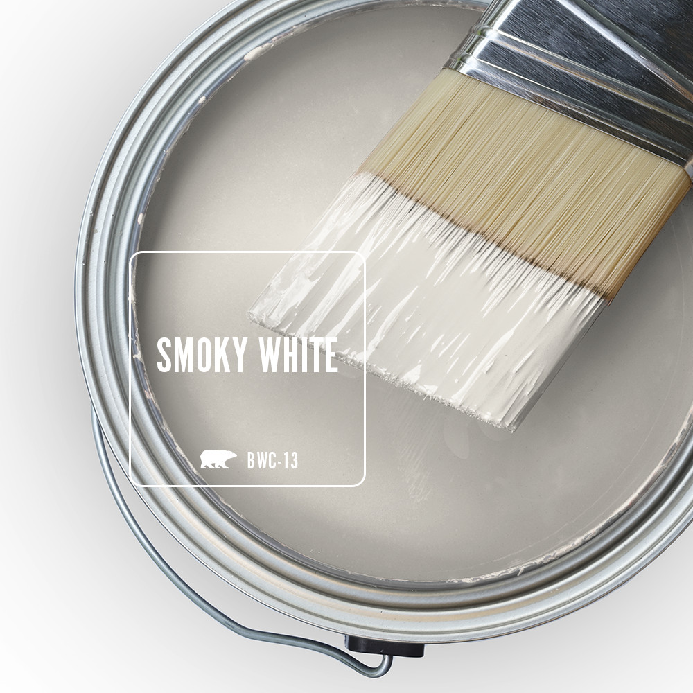 The top view of a paint can with a half dipped paint brush, the liquid paint inside the can is an off-white color called Smoky White.
