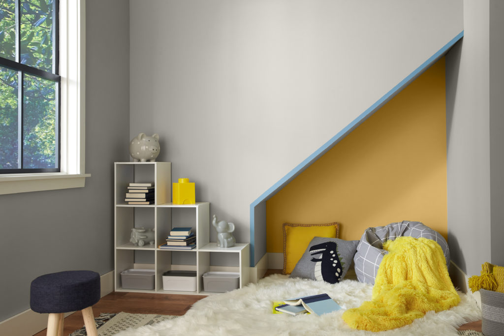 A modern cozy nook under the stairs.  The room is meant to be used as a kids play, sleep and relax area.  The main color of the wall is a light gray and the accent color are a bright yellow and a pastel blue. The decor elements include fluffy pillows and blankets.