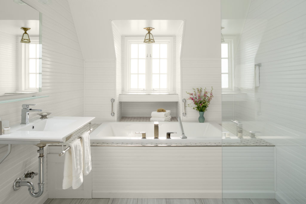 Cottage Style bathroom, the bead board on the wall is painted in all white paint. The bathtub and tile are also white.