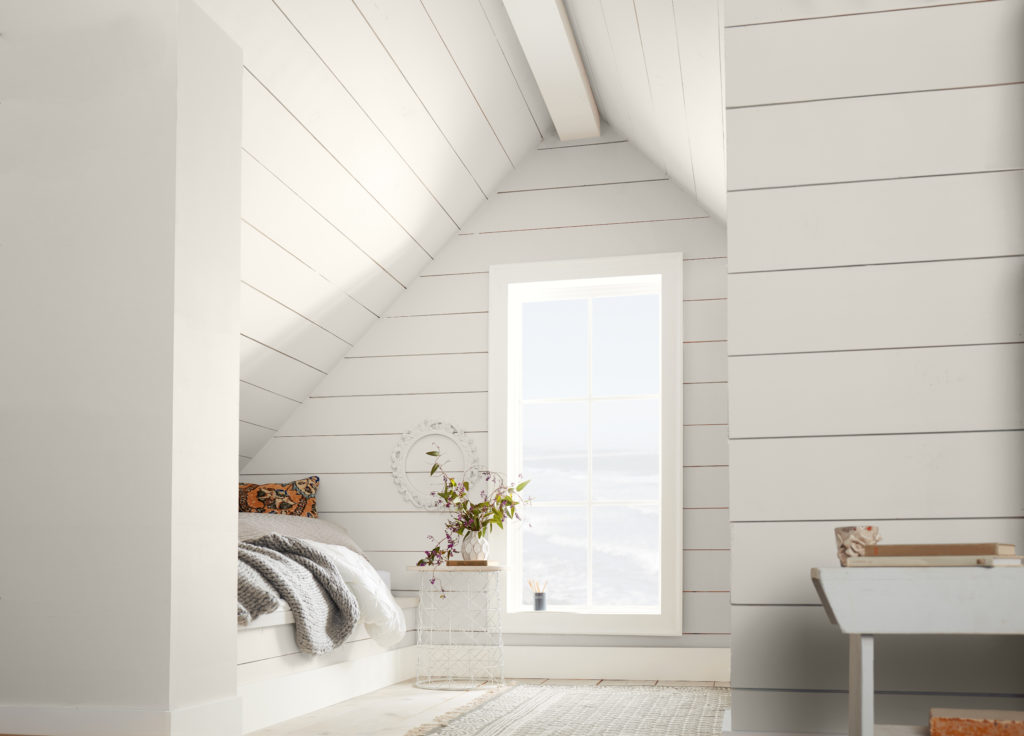 A cottage style bedroom the shiplap on the wall is painted in an off-white paint color called Smoky White.