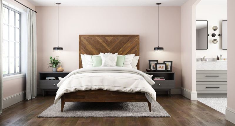 A  industrial-rustic master bedroom painted in a pink color, the bathroom next to the room features a gray painted sink which nicely coordinates with pink bedroom walls. The bed in the room is made of natural plant boards.