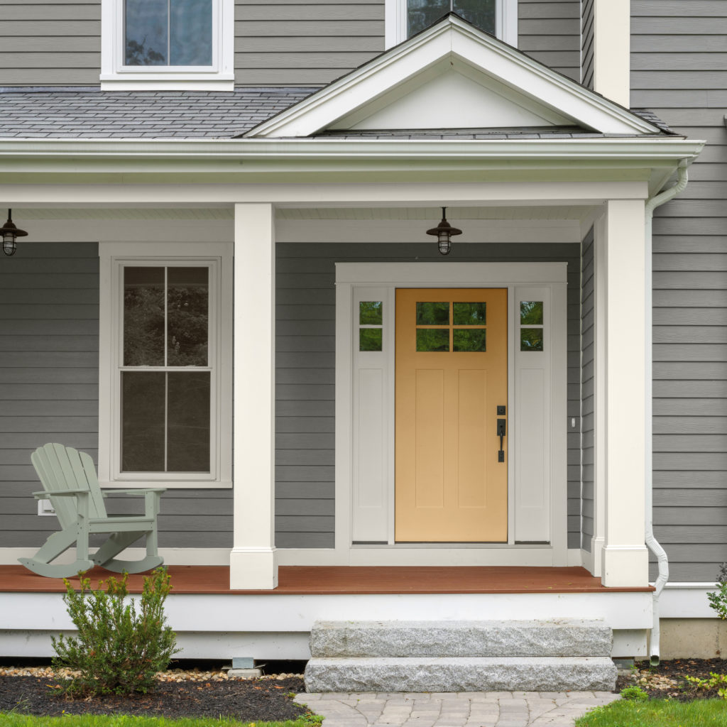 A gray house with a yellow painted front door.