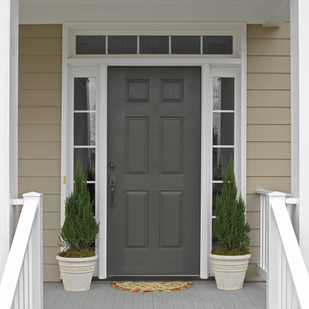 A light beige colored house with a dark charcoal colored door.