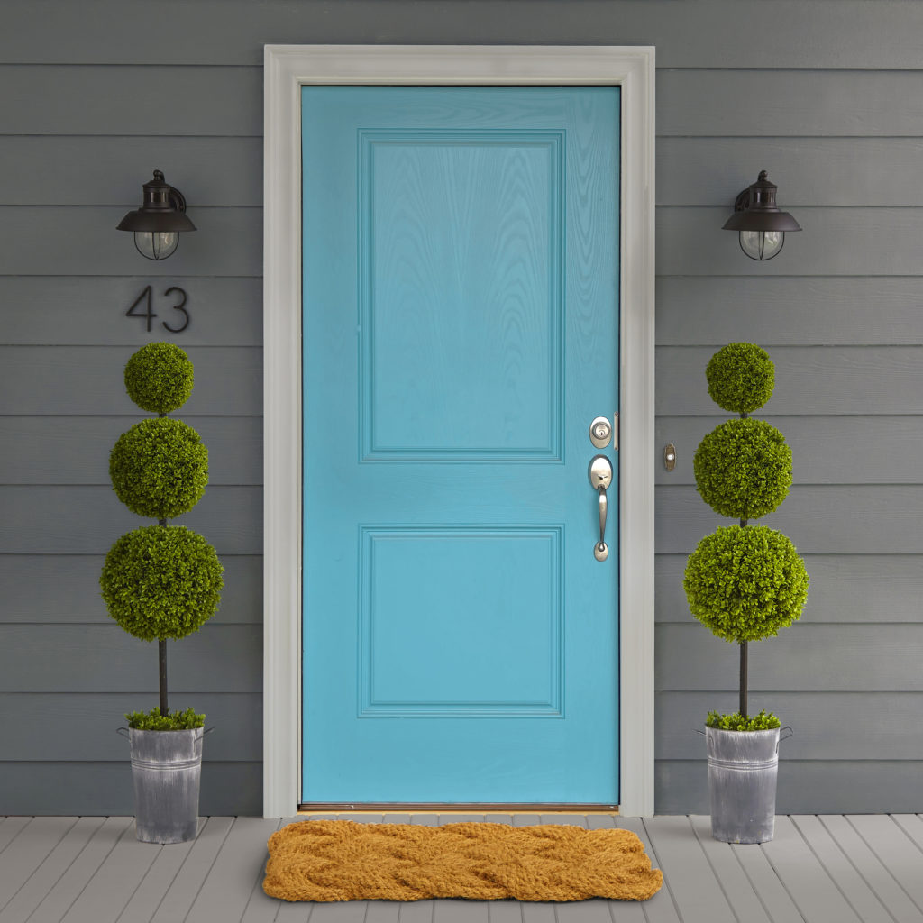 A housed painted in a dark charcoal color with a bright blue painted door.