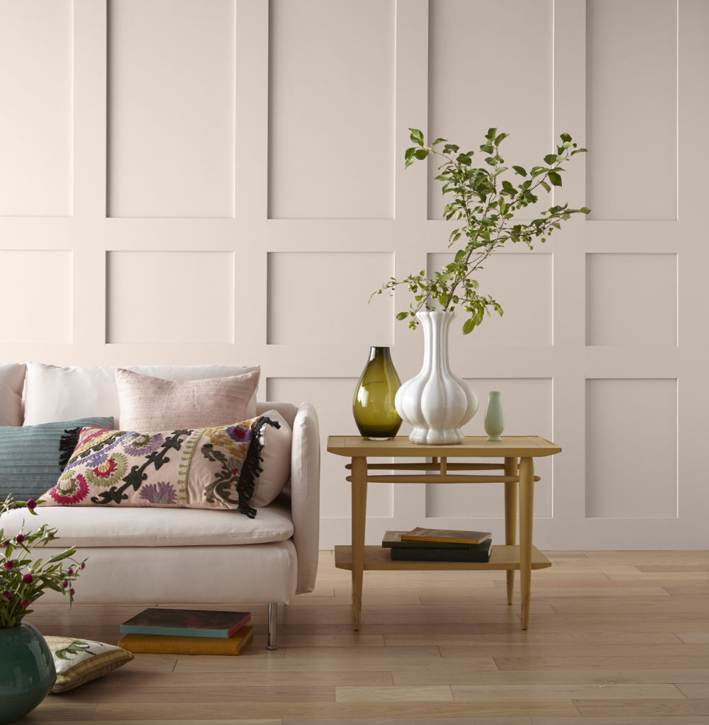An urban boho living room, there is a white sofa  and pillows in assorted patterns and textures in bolder colors.   Next to the sofa there is a natural wood tone side table with A few plants or a vase of flowers.